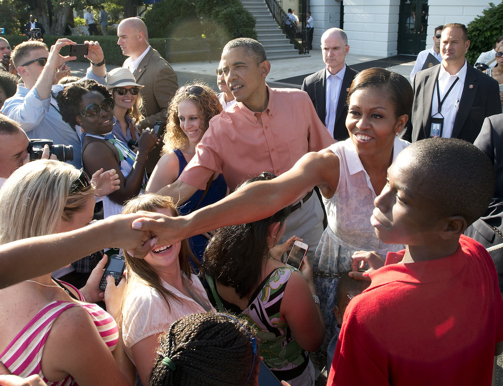 Description of . WASHINGTON, DC - JULY 04: U.S. President Barack Obama and first lady Michelle Obama work a rope line at a Fourth of July barbecue for military heroes and their families they are hosting on the South Lawn of the White House on July 4, 2013 in Washington, DC. The president and first lady are hosting members of the military and their families in commemoration of Independence Day. (Photo by Ron Sachs-Pool/Getty Images)