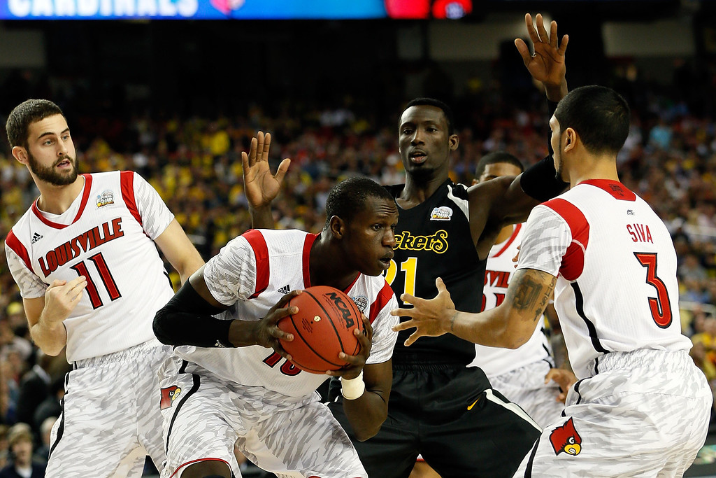 Description of . ATLANTA, GA - APRIL 06:  Gorgui Dieng #10 of the Louisville Cardinals controls a rebound in the first half against Ehimen Orukpe #21 of the Wichita State Shockers during the 2013 NCAA Men's Final Four Semifinal at the Georgia Dome on April 6, 2013 in Atlanta, Georgia.  (Photo by Kevin C. Cox/Getty Images)