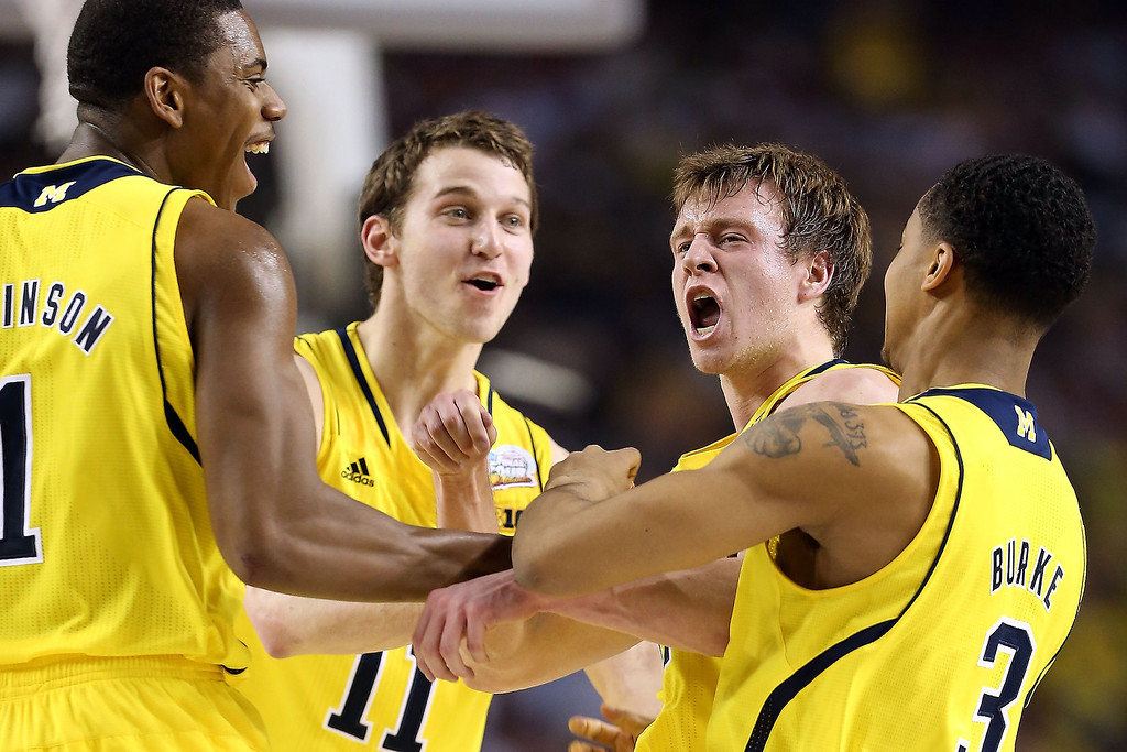 Description of . (From left) Glenn Robinson III #1, Nik Stauskas #11, Spike Albrecht #2 and Trey Burke #3 of the Michigan Wolverines celebrate a play in the first half against the Louisville Cardinals during the 2013 NCAA Men's Final Four Championship at the Georgia Dome on April 8, 2013 in Atlanta, Georgia.  (Photo by Andy Lyons/Getty Images)