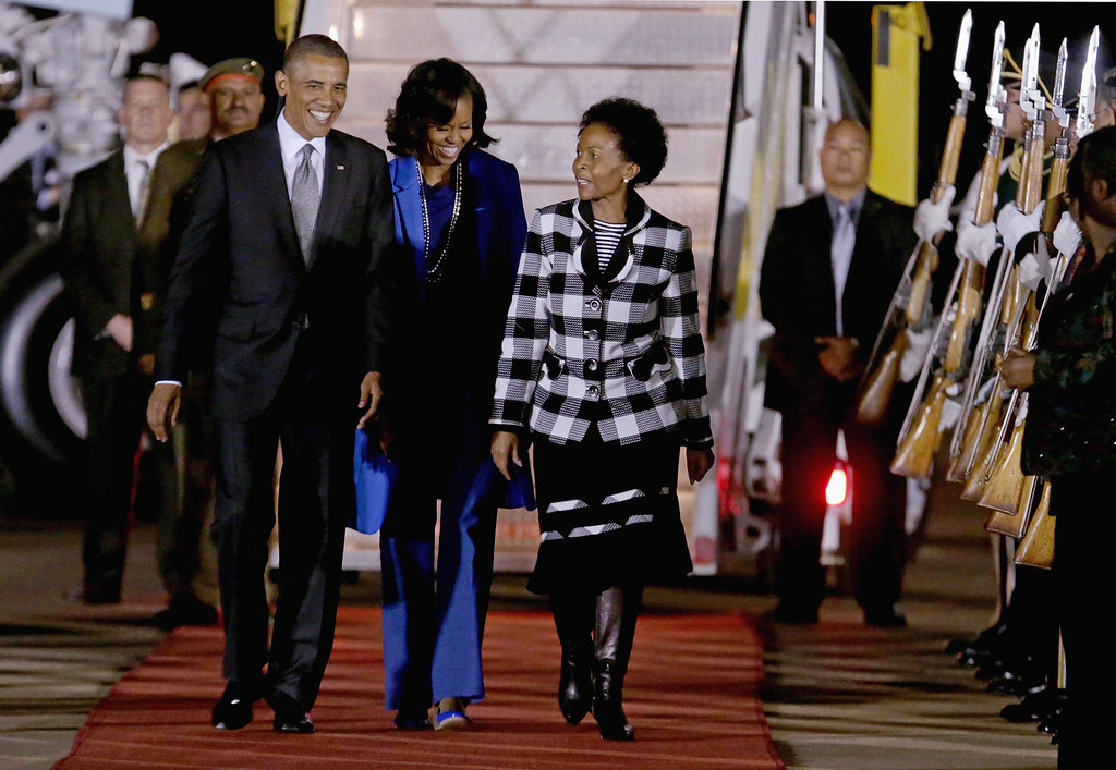 Description of . PRETORIA, SOUTH AFRICA - JUNE 28:  U.S. President Barack Obama (L) and first lady Michelle Obama (C) are greeted by Minister of International Relations and Cooperation Maite Mkoana-Mashabne after arriving at Waterkloof Air Force Base June 28, 2013 in Pretoria, South Africa. This is Obama's first official visit to South Africa, where is schedule to hold bilaterial meetings with President Jacob Zuma, host a town hall meeting with students in Soweto Township and visit Robben Island, where former President Nelson Mandela spent some of his 27 years in prison for fighting against apartheid.  (Photo by Chip Somodevilla/Getty Images)