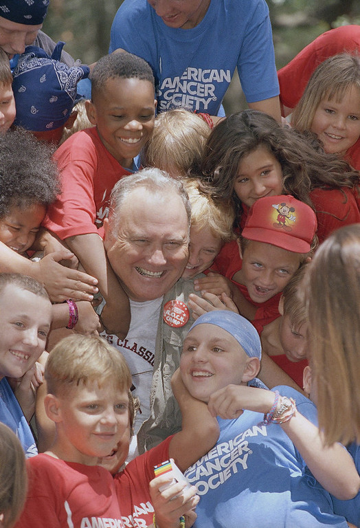 Description of . Retired General Norman Schwarzkopf is surrounded by campers during his visit to R.O.C.K., Reaching Out to Cancer Kids Camp on Tuesday, August 3, 1993 in Brandon, Fla. Schwarzkopf visited their barracks and joined in a sing along with the children ages 6 to 18. The cancer stricken kids enjoying the camp this week are from northern Florida. (AP Photo/Peter Cosgrove)