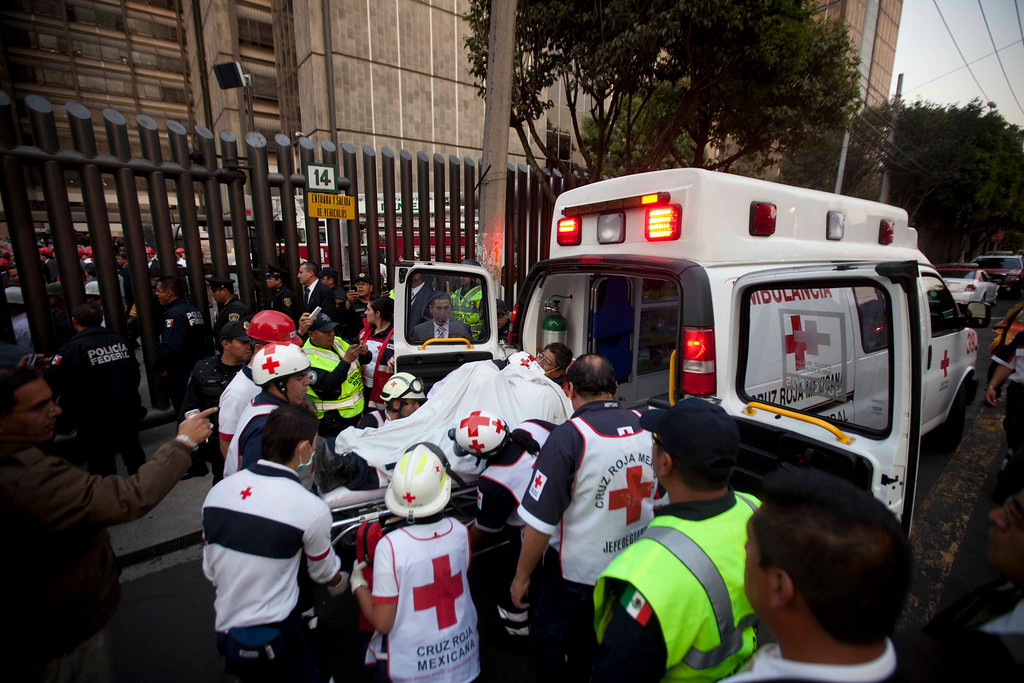 Description of . An injured person is carried into an ambulance after an explosion at an adjacent building to the executive tower of Mexico's state-owned oil company PEMEX, in Mexico City, Thursday Jan. 31, 2013.  (AP Photo/Eduardo Verdugo)