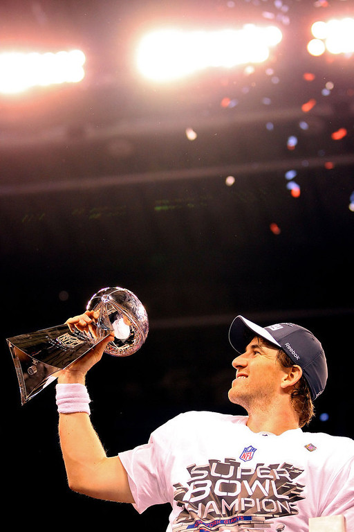 Description of . Quarterback Eli Manning #10 of the New York Giants poses with the Vince Lombardi Trophy after the Giants defeated the Patriots by a score of 21-17 in Super Bowl XLVI at Lucas Oil Stadium on February 5, 2012 in Indianapolis, Indiana.  (Photo by Ezra Shaw/Getty Images)