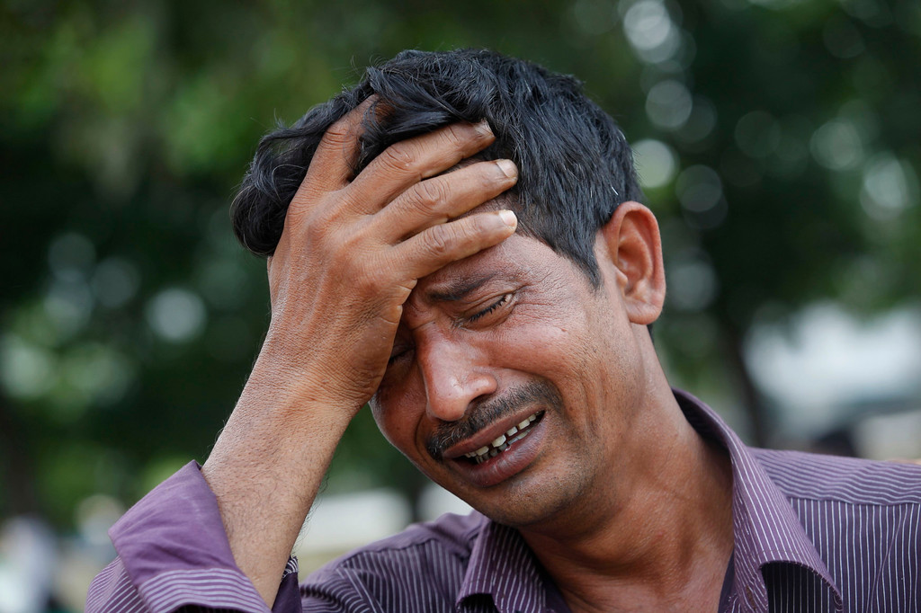 Description of . A man mourns for his relative, a garment worker who had died in the collapse of the Rana Plaza building, in Savar, around 30 km (19 miles) outside Dhaka April 30, 2013.  REUTERS/Andrew Biraj