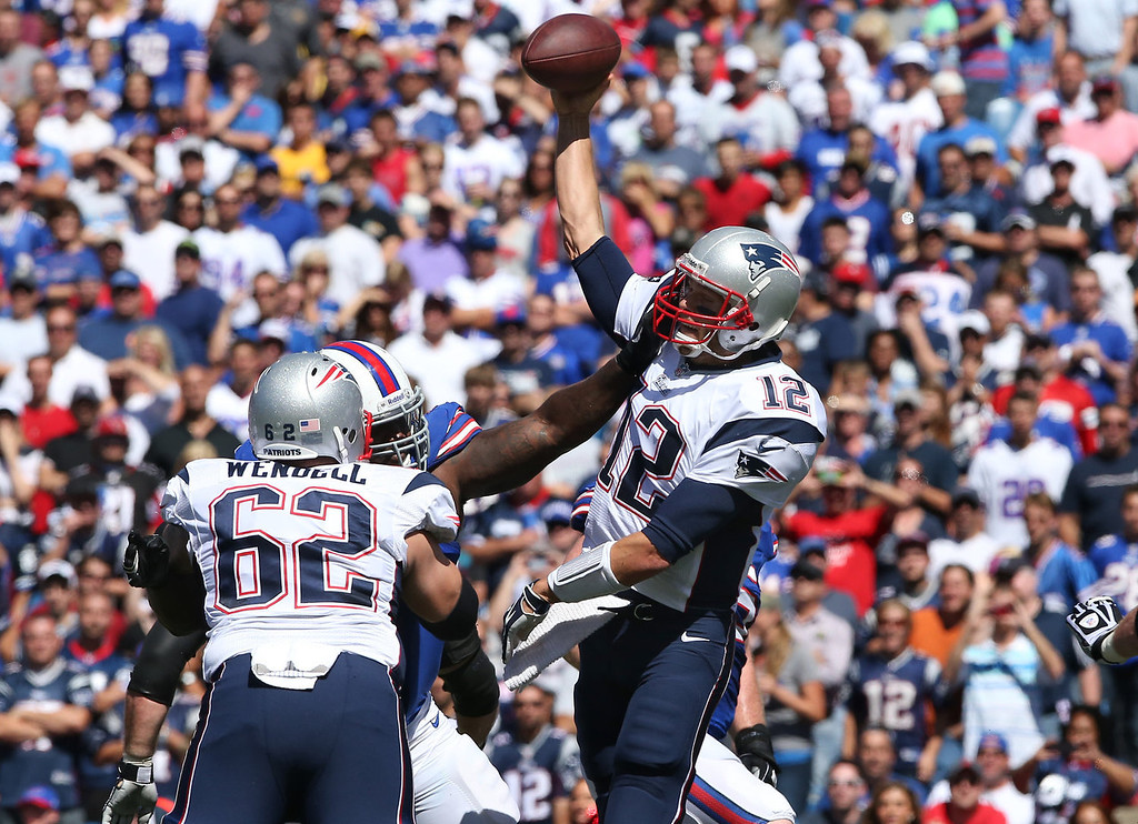Description of . Tom Brady #12 of the New England Patriots throws a pass under pressure during NFL game action against the Buffalo Bills at Ralph Wilson Stadium on September 8, 2013 in Orchard Park, New York. (Photo by Tom Szczerbowski/Getty Images)