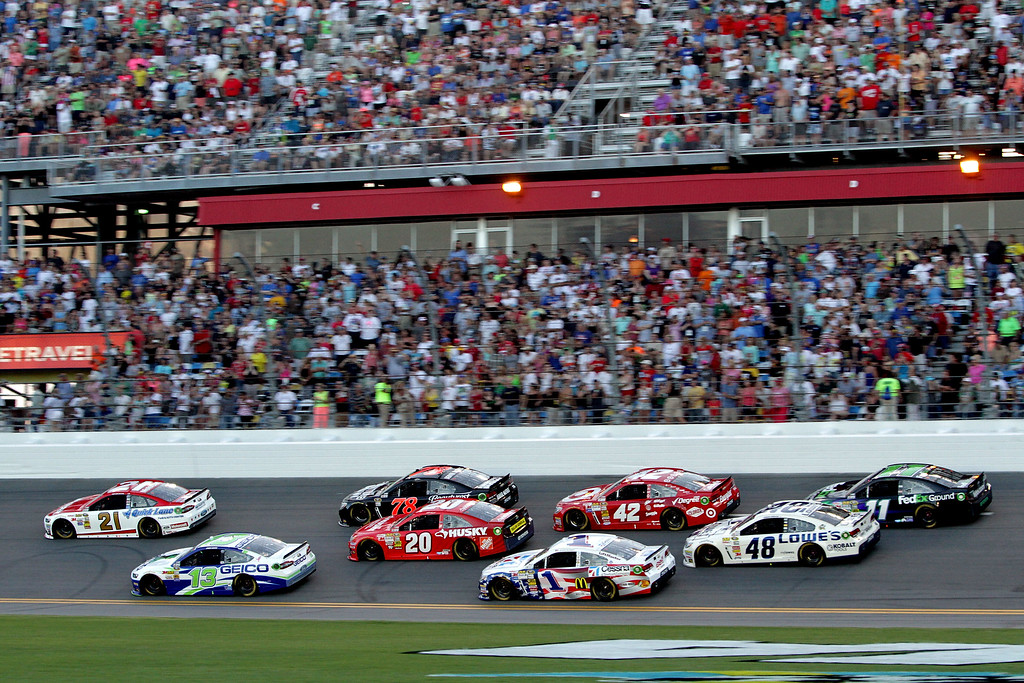Description of . DAYTONA BEACH, FL - JULY 06:  Trevor Bayne, driver of the #21 Motorcraft / Quick Lane Tire & Auto Center Ford, leads a pack of cars during the NASCAR Sprint Cup Series Coke Zero 400 at Daytona International Speedway on July 6, 2013 in Daytona Beach, Florida.  (Photo by Jerry Markland/Getty Images)