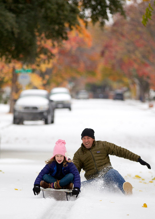 Description of . Mark Vogel gives his daughter Parker, 7, a push on the sled he used when he was a kid on the icy streets in Fort Worth, Texas on Friday, Dec. 6, 2013. Winter storm and ice warnings are in effect through much of today for parts of six states in the Midwest, including Texas, Missouri, Illinois and Indiana. (AP Photo/The Fort Worth Star-Telegram, Joyce Marshall)