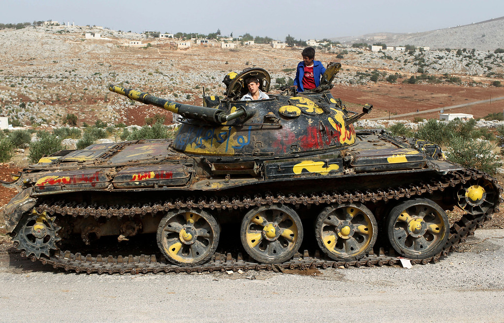 Description of . Children play on a tank that belonged to pro-government forces in an area controlled by the Free Syrian Army in Idlib Governorate, October 21, 2012. REUTERS/Asmaa Waguih (
