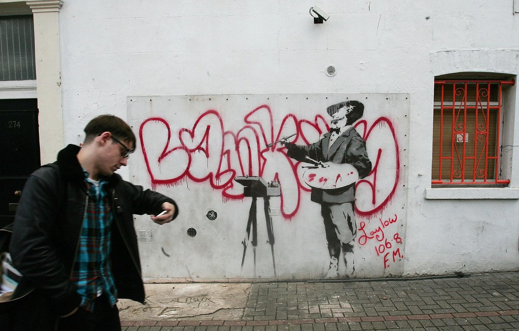 Description of . A man walks past a graffiti mural by British artist Banksy, spraypainted on a wall on Portobello road in London, 14 January 2008. The wall has been put up for bid on the internet auction site Ebay. The successful bidder must also cover the cost of the wall's removal and delivery. The wall has reached a price of 1,000,000 GBP. (CARL DE SOUZA/AFP/Getty Images)