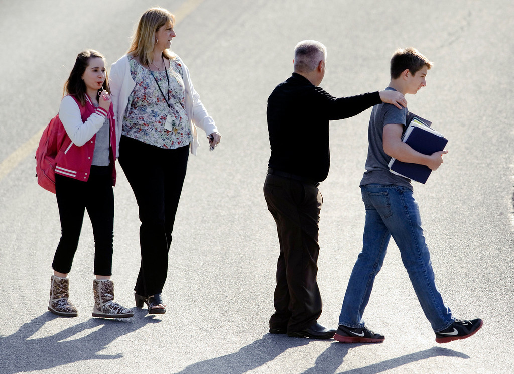 Description of . Students and guardians walk to their car from the Franklin Regional Middle School after more then a dozen students were stabbed by a knife wielding suspect at Franklin Regional High School on Wednesday, April 9, 2014, in Murrysville, Pa., near Pittsburgh. The suspect, a male student, was taken into custody and is being questioned. (AP Photo/Tribune Review, Brian F. Henry)