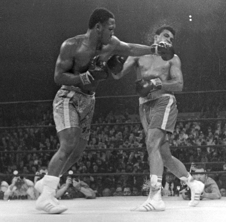 Description of . In this March 8, 1971, file photo, Muhammad Ali. right, takes a left from Joe Frazier during the 15th round of their heavyweight title boxing bout in New York. Frazier won a unanimous decision.   Frazier, the former heavyweight champion who handed Ali his first defeat yet had to live forever in his shadow, died Monday Nov. 7, 2011 after a brief  fight with liver cancer. He was 67. (AP Photo/File)