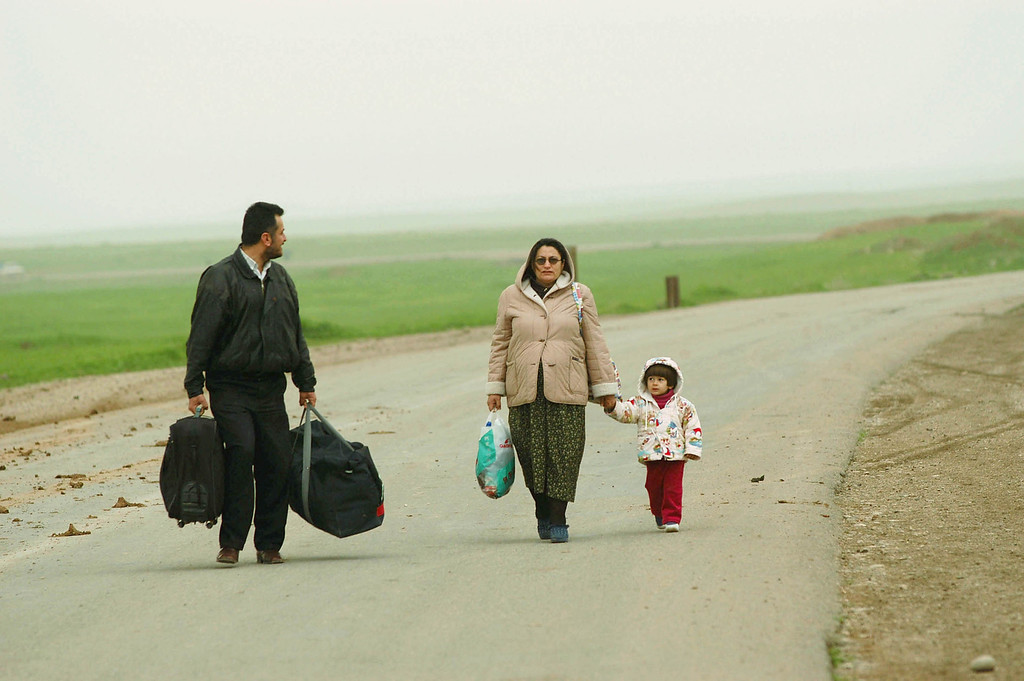 Description of . A father from Baghdad flees Iraq with his pregnant wife and daughter at the Qoshtapa checkpoint near Erbil. The threat of war created a constant stream of refugees into Northern Iraq. (Photo Patrick Barth/Getty Images)