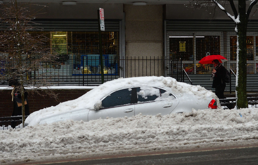 Description of . A car is buried  after an overnight snow storm followed by freezing rain in New York, February 5, 2014.  AFP PHOTO/Emmanuel DUNAND/AFP/Getty Images