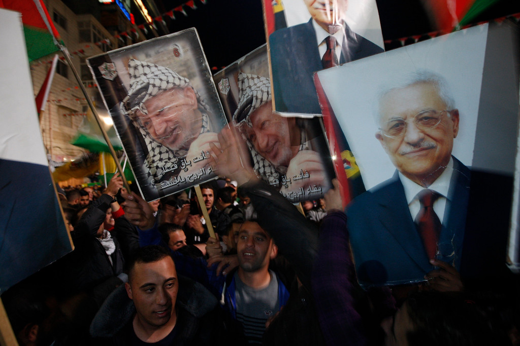 Description of . Palestinians celebrate as they wave posters of former Palestinian leader Yasser Arafat, left, and President Mahmoud Abbas, right, as they watch the U.N. General Assembly votes on a resolution to upgrade the status of the Palestinian Authority to a nonmember observer state, in the west bank city of Ramallah, Thursday, Nov. 29, 2012.  The U.N. General Assembly has voted by a more than two-thirds majority to recognize the state of Palestine. The resolution upgrading the Palestinians' status to a nonmember observer state at the United Nations was approved by the 193-member world body late Thursday by a vote of 138-9 with 41 abstentions. (AP Photo/Majdi Mohammed)