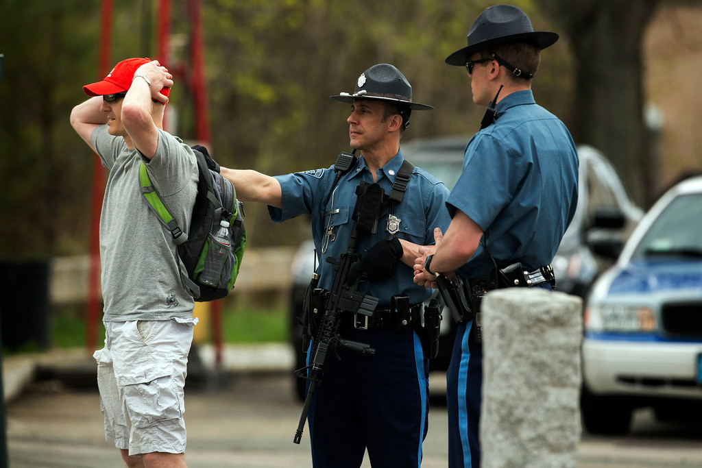 Description of . Law enforcement officers briefly detain a suspect to verify his ID on Arsenal St, in the search area for Dzhokar Tsarnaev, the one remaining suspect in the Boston Marathon bombing, in Watertown, Massachusetts April 19, 2013. REUTERS/Lucas Jackson