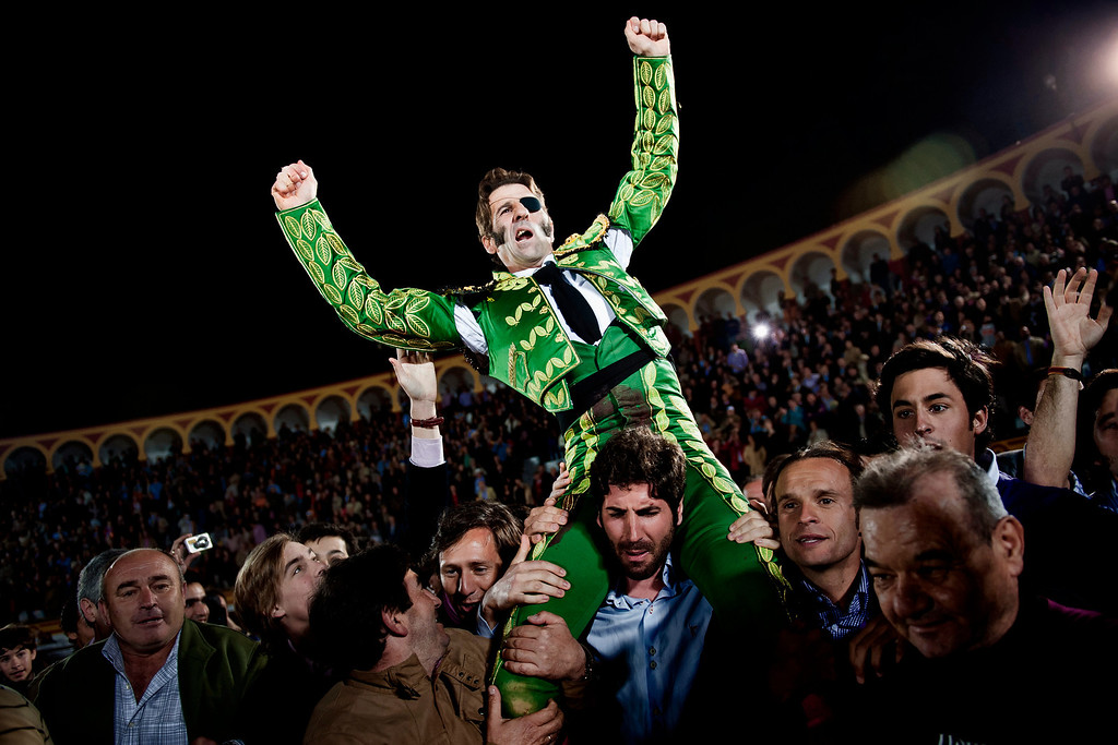 Description of . In this March 4, 2012 photo, Spanish bullfighter Juan Jose Padilla is carried out of the ring among jubilant crowd scenes on the shoulders of fellow bullfighter Serafin Marin, a honor for the best performers, after a bullfight at the southwestern Spanish town of Olivenza. This photo is one in a series of images by Associated Press photographer Daniel Ochoa de Olza that won the second place prize for the Observed Portrait series category in the World Press Photo 2013 photo contest.  (AP Photo/Daniel Ochoa de Olza, File)