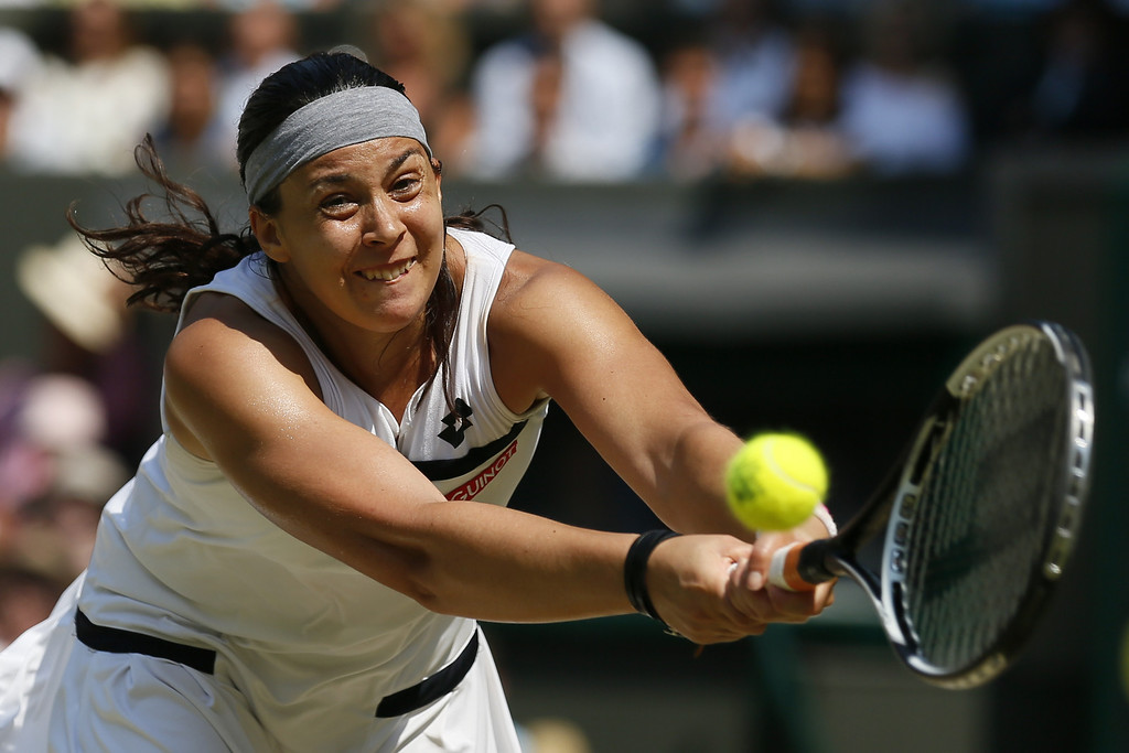 Description of . France's Marion Bartoli returns against Germany's Sabine Lisicki in their women's singles final match on day twelve of the 2013 Wimbledon Championships tennis tournament at the All England Club in Wimbledon, southwest London, on July 6, 2013.  STEFAN WERMUTH/AFP/Getty Images