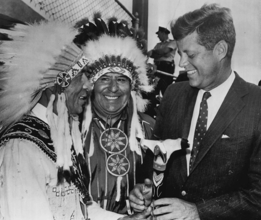 Description of . Sen. Kennedy receives a gift war club from Joseph Ranco, left, of the Penobscot tribe and Bruce Poolaw in September 1960 during a campaign tour of Maine.  Denver Post file