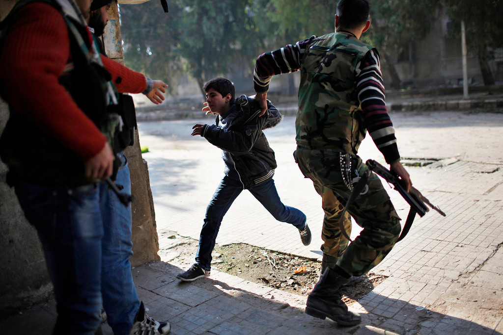 Description of . A Free Syrian Army fighter pulls a boy off the street as a sniper fires during fighting with forces loyal to Syrian President Bashar el-Assad in Aleppo city December, 31, 2012. REUTERS/Ahmed Jadallah