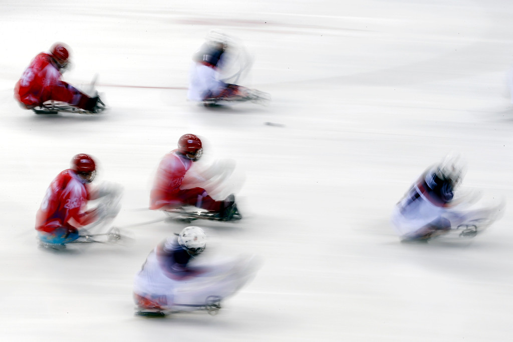 Description of . South Korea and United States players in action during their ice sledge hockey match at the 2014 Winter Paralympics in Sochi, Russia, Sunday March 9, 2014. United States won the match 3-0. (AP Photo/Pavel Golovkin)