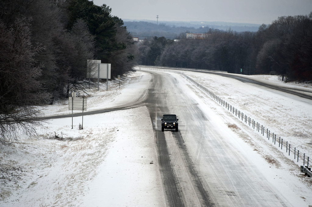 Description of . With one lane cleared of snow and ice, a car drives north on I-85 , February 13, 2014 near Braselton, Georgia. Gov. Nathan Deal declared a state of emergency for 14 counties due to the winter storm. (Photo by Davis Turner/Getty Images)