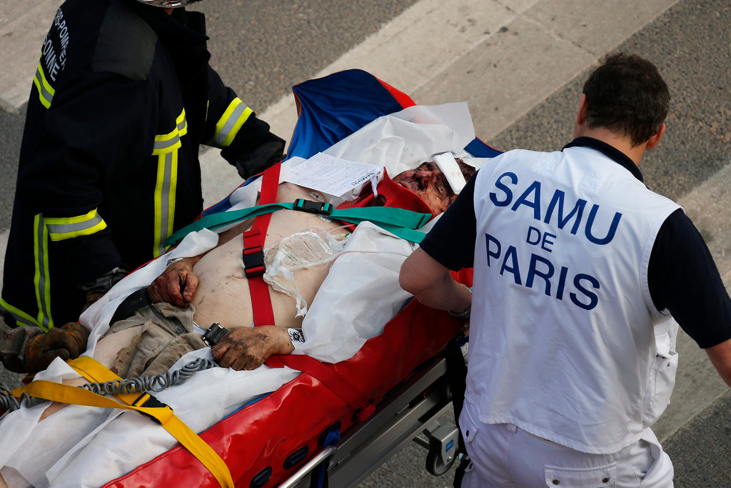 Description of . A fireman and a rescue worker evacuate an injured man after an intercity train accident at the Bretigny-sur-Orge train station near Paris July 12, 2013.  REUTERS/Benoit Tessier
