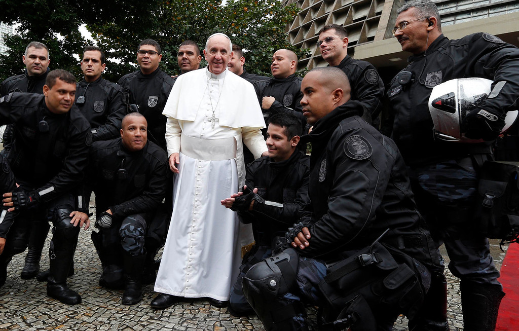 Description of . Pope Francis poses for a picture with military policemen outside the Metropolitan cathedral in Rio de Janeiro on July 25, 2013. The first Latin American and Jesuit pontiff arrived in Brazil mainly for the huge five-day Catholic gathering World Youth Day.  STEFANO RELLANDINI/AFP/Getty Images