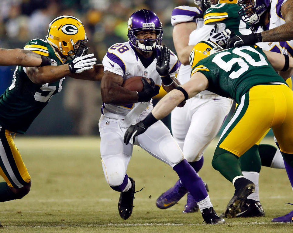 Description of . Minnesota Vikings running back Adrian Peterson (28) finds a hole between Green Bay Packers inside linebacker A.J. Hawk (50) and linebacker Brad Jones (59) during their NFL NFC wildcard playoff football game in Green Bay, Wisconsin January 5, 2013.  REUTERS/Tom Lynn