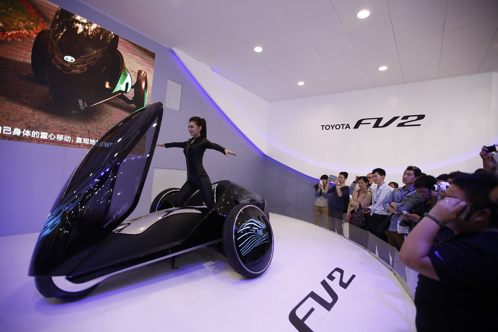 Description of . A model (C) poses on a Toyota FV2 concept car at the China International Exhibition Center new venue during the