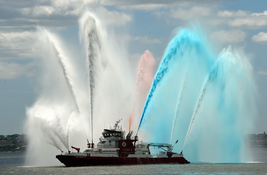 Description of . The New York City fireboat sprays colored water into the New York Harbor June 6, 2014 in New York. Thousands gathered on the Liberty Island to participate in ceremonies commemorating the 70th anniversary of D-Day. AFP PHOTO/Don EMMERT/AFP/Getty Images