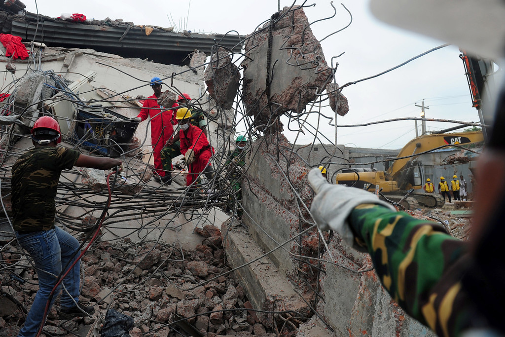 Description of . Bangladeshi rescuers work as Bangladeshi Army personnel continue the second phase of the rescue operation using heavy equipment after an eight-story building collapsed in Savar, on the outskirts of Dhaka, on April 30, 2013. AFP PHOTO/ MUNIR UZ ZAMAN/AFP/Getty Images
