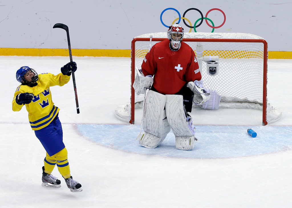 Description of . Erica Uden Johansson of Sweden (21)reacts after scoring a goal on goalkeeper Florence Schelling of Switzerland (41) during the women's bronze medal ice hockey game at the 2014 Winter Olympics, Thursday, Feb. 20, 2014, in Sochi, Russia. (AP Photo/David J. Phillip )