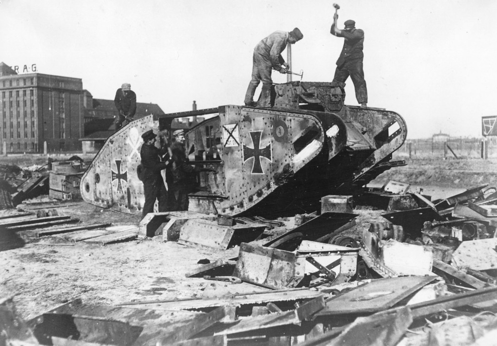 Description of . 1919:  Germans take war machines apart outside Berlin.  Under the terms of the Treaty of Versailles Germany was required to disarm.  This tank is in fact a British tank, captured and put into service by the Germans.  (Photo by Hulton Archive/Getty Images)