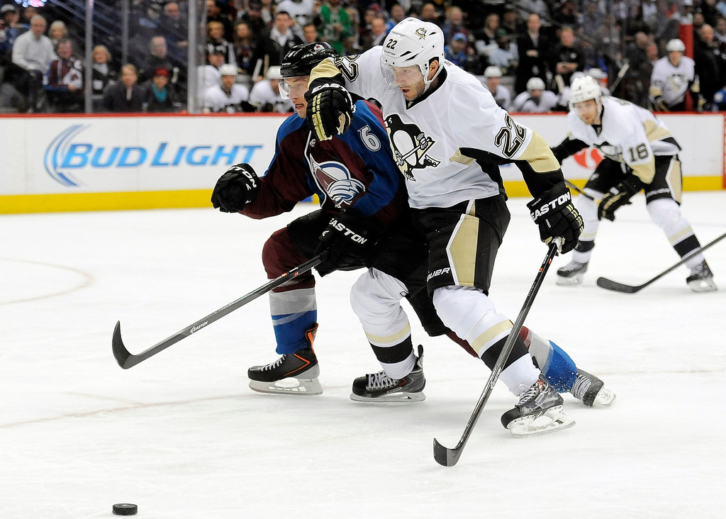 Description of . Colorado Avalanche defenseman Erik Johnson, left, and Pittsburgh Penguins right wing Lee Stempniak, right, vie for the puck during the second period of an NHL hockey game on Sunday, April 6, 2014, in Denver. The Penguins won 3-2 in a shootout. (AP Photo/Chris Schneider)