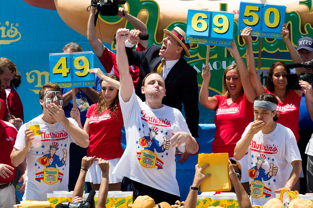 Description of . Joey Chestnut, center, wins the Nathan's Famous Fourth of July International Hot Dog Eating contest with a total of 69 hot dogs and buns, alongside Tim Janus, left, and Matt Stonie, right, Thursday, July 4, 2013 at Coney Island, in the Brooklyn borough of New York. (AP Photo/John Minchillo)