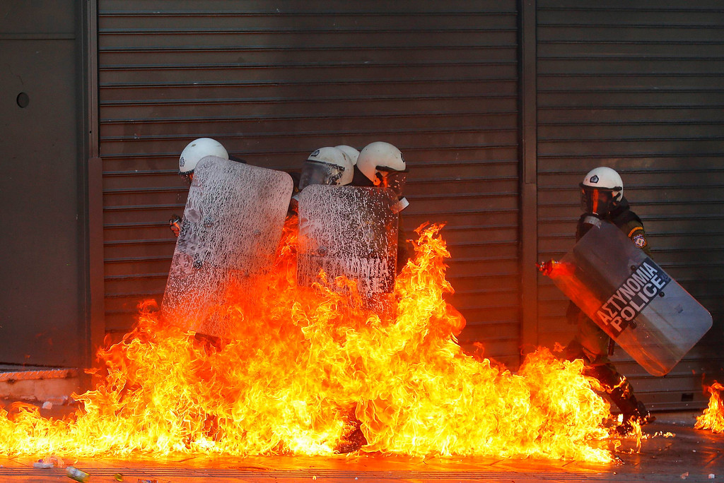 Description of . A group of riot policemen is engulfed in flames after protesters threw petrol bombs in Athens' Syntagma square during a 24-hour labour strike September 26, 2012. Greek police fired teargas at hooded youths hurling petrol bombs and stones as tens of thousands took to the streets in Greece's biggest anti-austerity demonstration in months on Wednesday. The officers escaped with little to no injuries. REUTERS/Yannis Behrakis