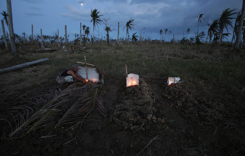 Description of . A survivor lights candles on a makeshift grave site of his father and uncle, left, on a field in Palo town, Leyte province, central Philippines on Saturday, Nov. 16, 2013. Residents decided to bury bodies of relatives and unknown people killed during Typhoon Haiyan on the field because they have started to decay and may pose a health risk. (AP Photo/Aaron Favila)
