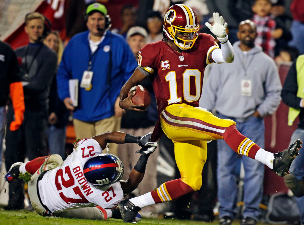 Description of . Washington Redskins quarterback Robert Griffin III (10) is pulled down by New York Giants strong safety Stevie Brown (27) during the second half of an NFL football game in Landover, Md., Monday, Dec. 3, 2012. (AP Photo/Evan Vucci)
