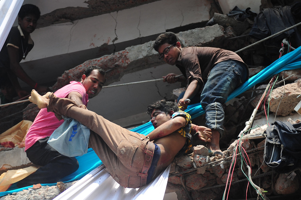 Description of . Volunteers carry the body of a garment worker after an eight-story building collapsed in Savar, on the outskirts of Dhaka, on April 24, 2013.   AFP PHOTO/Munir uz ZAMAN/AFP/Getty Images