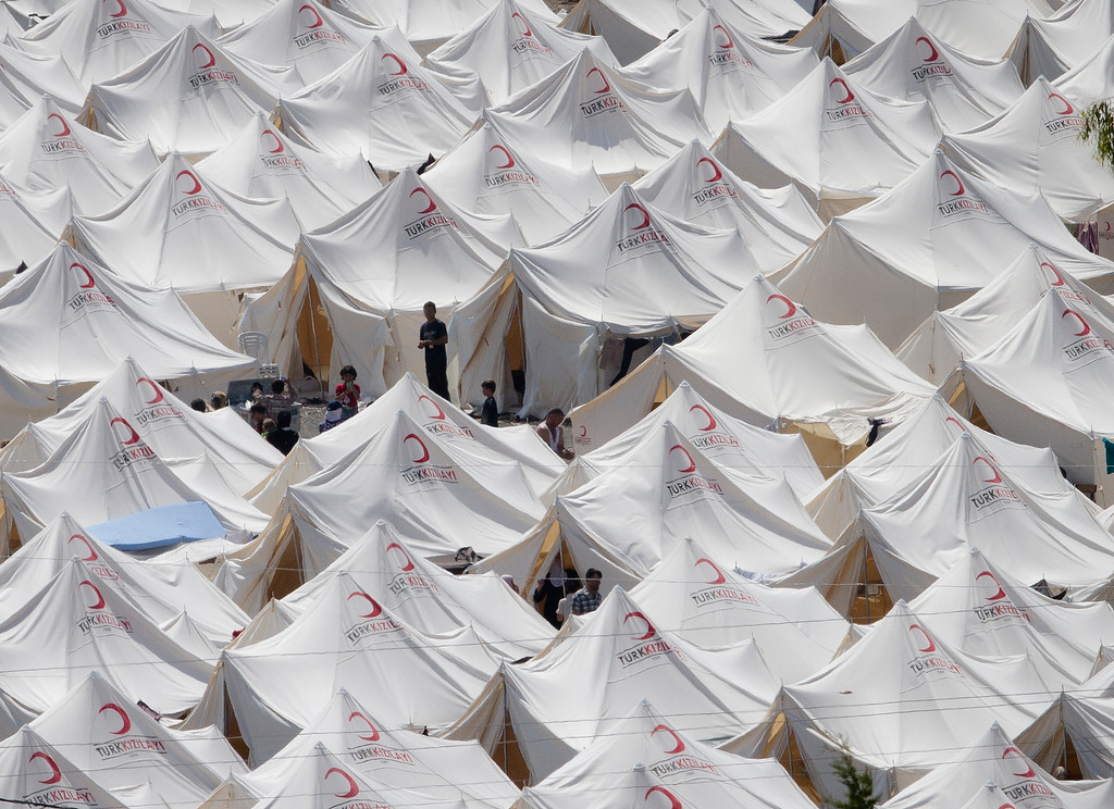 Description of . Syrian refugees are seen inside a tented refugee city, in Boynuyogun, Turkey, Saturday, June 18, 2011, before a brief visit organized by Turkish authorities for the media. According to Turkish authorities more than 10,000 Syrians are now in refugee camps in the Hatay province, near Turkey's border with Syria.(AP Photo/Vadim Ghirda)