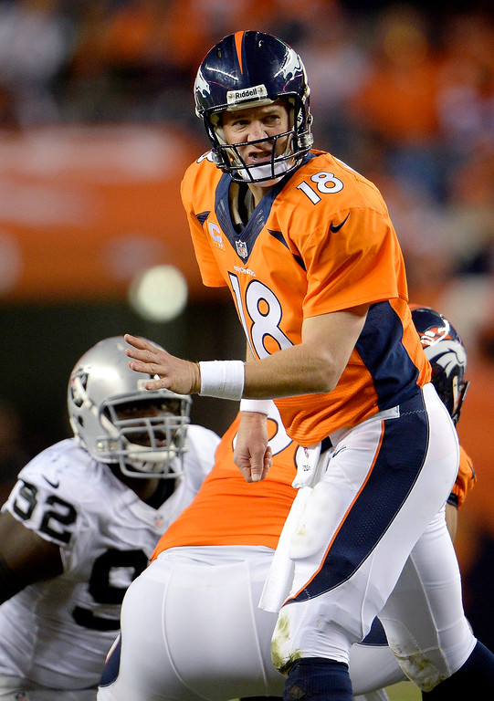 Description of . Denver Broncos quarterback Peyton Manning (18) runs the offense during the fourth quarter in a game the Broncos would win 37-21. The Denver Broncos took on the Oakland Raiders at Sports Authority Field at Mile High in Denver on September 23, 2013. (Photo by Joe Amon/The Denver Post)