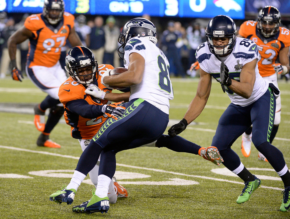 Description of . Denver Broncos free safety Mike Adams (20) gets a hold of Seattle Seahawks wide receiver Golden Tate (81) during the third quarter. The Denver Broncos vs the Seattle Seahawks in Super Bowl XLVIII at MetLife Stadium in East Rutherford, New Jersey Sunday, February 2, 2014. (Photo by John Leyba/The Denver Post)