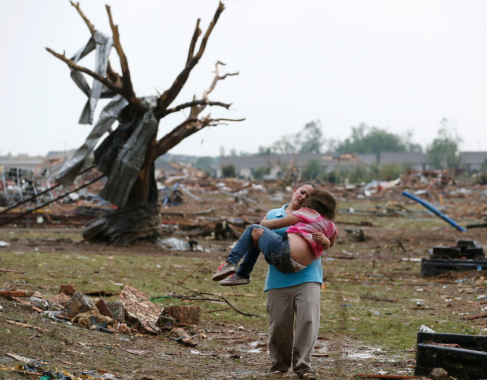 Description of . In this May 20, 2013, file photo, LaTisha Garcia carries her 8-year-old daughter, Jazmin Rodriguez, near Plaza Towers Elementary School after a massive tornado carved its way through Moore, Okla., leaving little of the school and neighborhood. (AP Photo/Sue Ogrocki, File)
