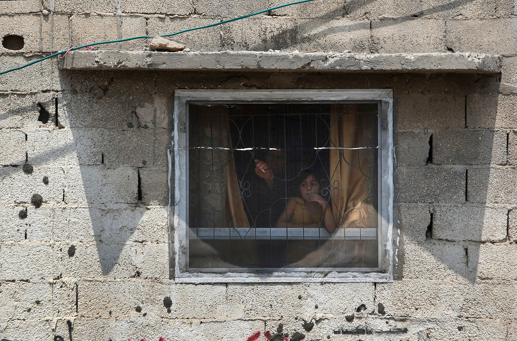 Description of . Palestinians watch as mourners leave after the funeral of seven members of the Kelani family in Beit Lahiya, northern Gaza Strip, on Tuesday, July 22, 2014. Ibrahim Kelani, 53, his wife, Taghreed, and their five children were killed overnight in a strike on a Gaza City high-rise. Ibrahim's brother Saleh Kelani said Tuesday that his brother and his brother's children, ranging in age from 4 to 12, had German citizenship, but his wife did not. The family had rented the apartment in the high-rise after fleeing their home in the northern Gaza town of Beit Lahiya which came under heavy shelling by the Israeli army. (AP Photo/Majed Hamdan)