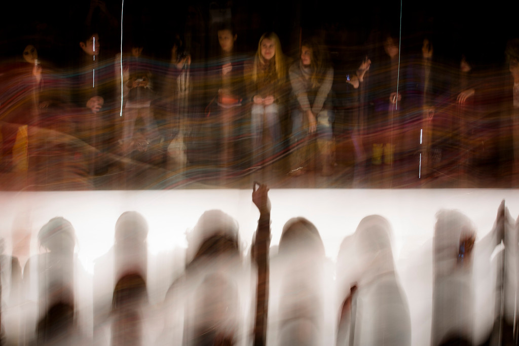. In this photo made with a long exposure, an audience member takes a photograph with a cell phone as the Mara Hoffman Fall 2013 collection is shown at the Mercedes-Benz Fashion Week tents at Lincoln Center, Saturday, Feb. 9, 2013, in New York. (AP Photo/John Minchillo)
