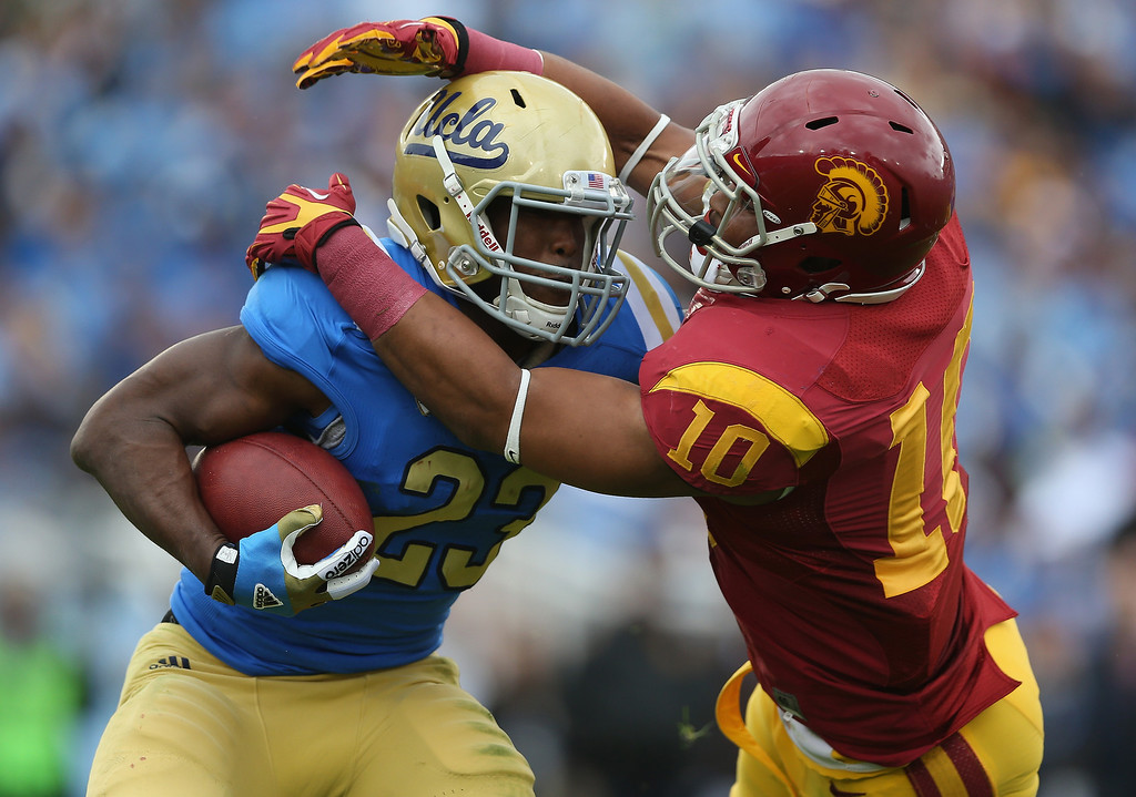 Description of . Running back Johnathan Franklin #23 of the UCLA Bruins is tackled by linebacker Hayes Pullard #10 of the USC Trojans in the first half against the USC Trojans at the Rose Bowl on November 17, 2012 in Pasadena, California.  (Photo by Jeff Gross/Getty Images)