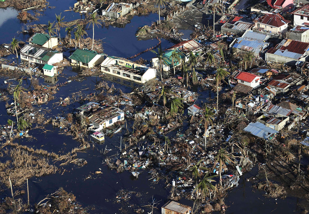 Description of . Damaged houses lie in a flooded area in this aerial photo taken from a Philippine Air Force helicopter in typhoon-ravaged Leyte province, central Philippines Monday, Nov. 18, 2013. Hundreds of thousands of people were displaced by Typhoon Haiyan, which tore across several islands in the eastern Philippines on Nov. 8. (AP Photo/Aaron Favila)