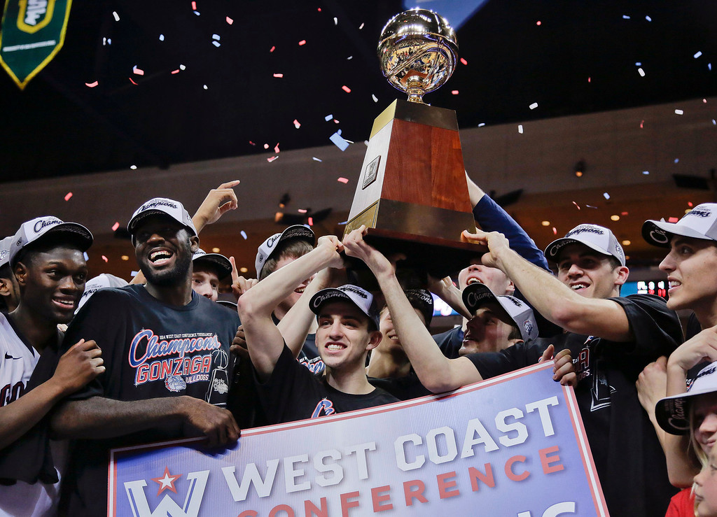 Description of . Gonzaga players hold up the championship trophy after defeating BYU 75-64 in an NCAA college basketball game for the West Coast Conference men's tournament title, Tuesday, March 11, 2014, in Las Vegas. (AP Photo/Julie Jacobson)