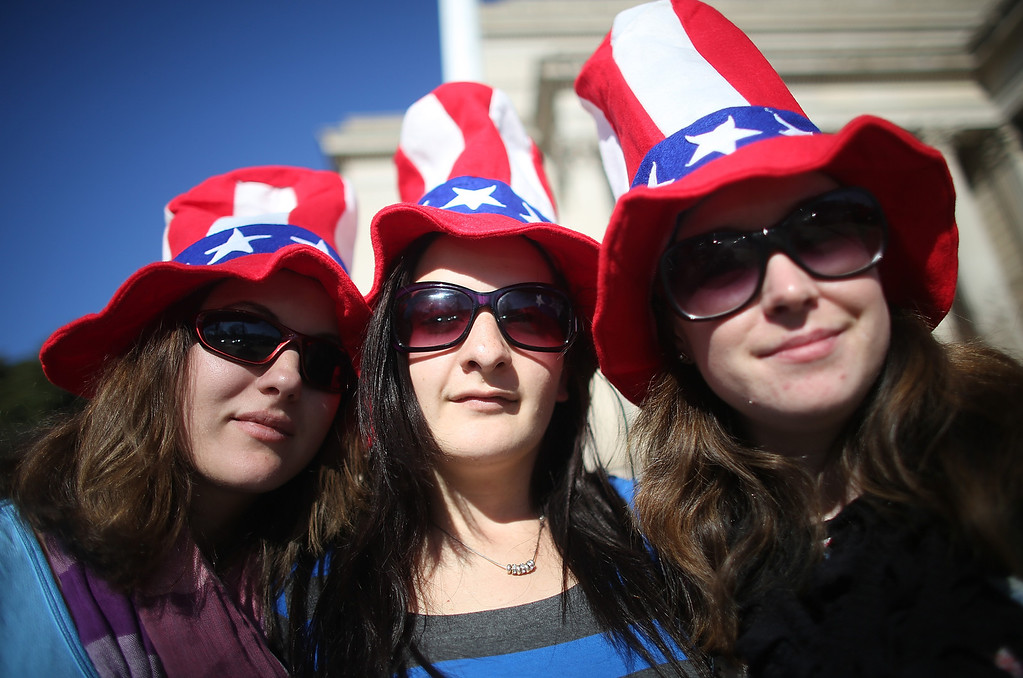 Description of . (L to R) Bek Russell, Jane Heard and Emma Llewellyn, tourists from Australia, pose while sporting Uncle Sam hats as Washington prepares for U.S. President Barack Obama's second inauguration on January 20, 2013 in Washington, DC.  One day before the public inaugural ceremony at the U.S. Captiol on January 21, Obama was officially sworn in for his second term during a private ceremony surrounded by friends and family in the Blue Room of the White House.  (Photo by Mario Tama/Getty Images)