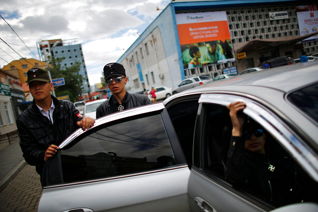 Description of . Members of the Mongolian neo-Nazi group Tsagaan Khass leave their headquarters in Ulan Bator June 23, 2013. The group has rebranded itself as an environmentalist organisation fighting pollution by foreign-owned mines, seeking legitimacy as it sends Swastika-wearing members to check mining permits.Over the past years, ultra-nationalist groups have expanded in the country and among those garnering attention is Tsagaan Khass, which has recently shifted its focus from activities such as attacks on women it accuses of consorting with foreign men to environmental issues, with the stated goal of protecting Mongolia from foreign mining interests. This ultra-nationalist group was founded in the 1990s and currently has 100-plus members. Picture taken June 23, 2013.  REUTERS/Carlos Barria